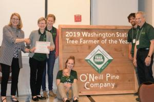 Pines receiving Tree Farmer of Year Sign